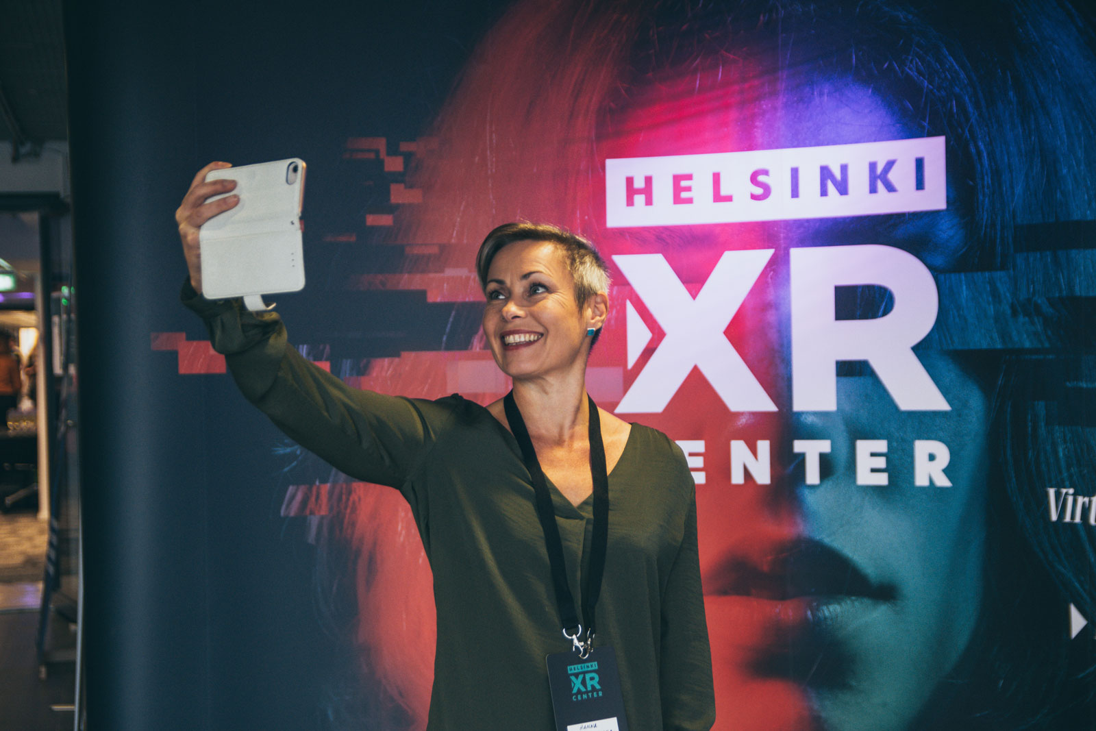 Hanna Pajala-Assefa from Skeleton Conductor taking a selfie with Helsinki XR Center banner at HXRC Grand Opening on 5 September 2019.