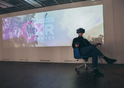 A person in VR headset is sitting comfortably in a chair. Behind in is an image projection with Helsinki XR Center logo.