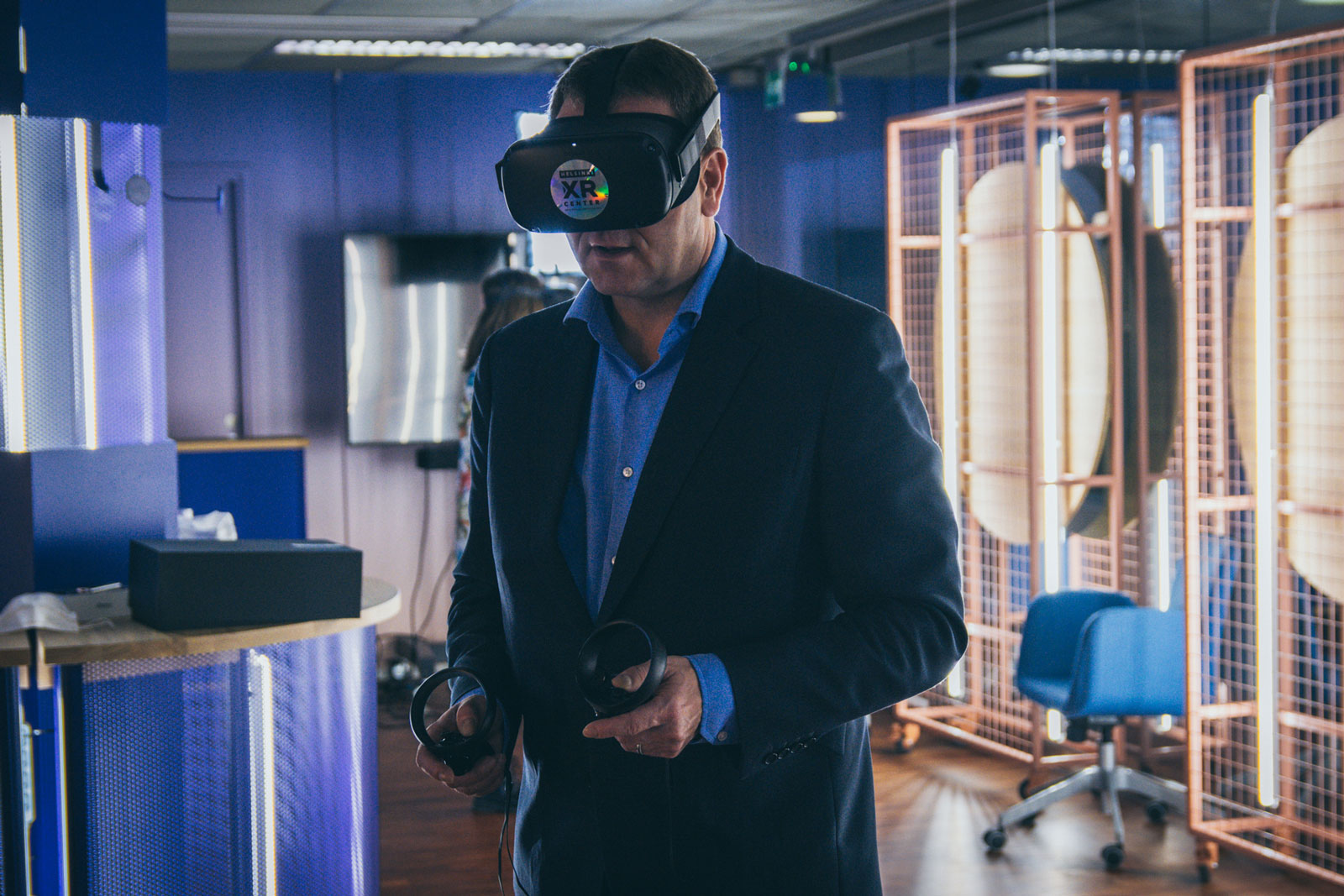 Jan Vapaavuori, Mayor of Helsinki, is standing with a VR headset and controllers.