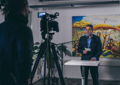 On the left there is a cameraperson with a camera on a tripod. On the right, Jan Vapaavuori, the Mayor of Helsinki, is standing in front of a microphone with a paper in his hand, speaking into the camera. Behind him is a big, colourful painting behind him.