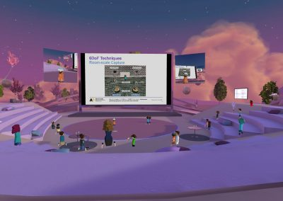 Lilac amphitheater in a virtual reality environment AltspaceVR. There is a big screen in the middle, with a presentation going on. Around it are virtual human avatars watching the presentation.
