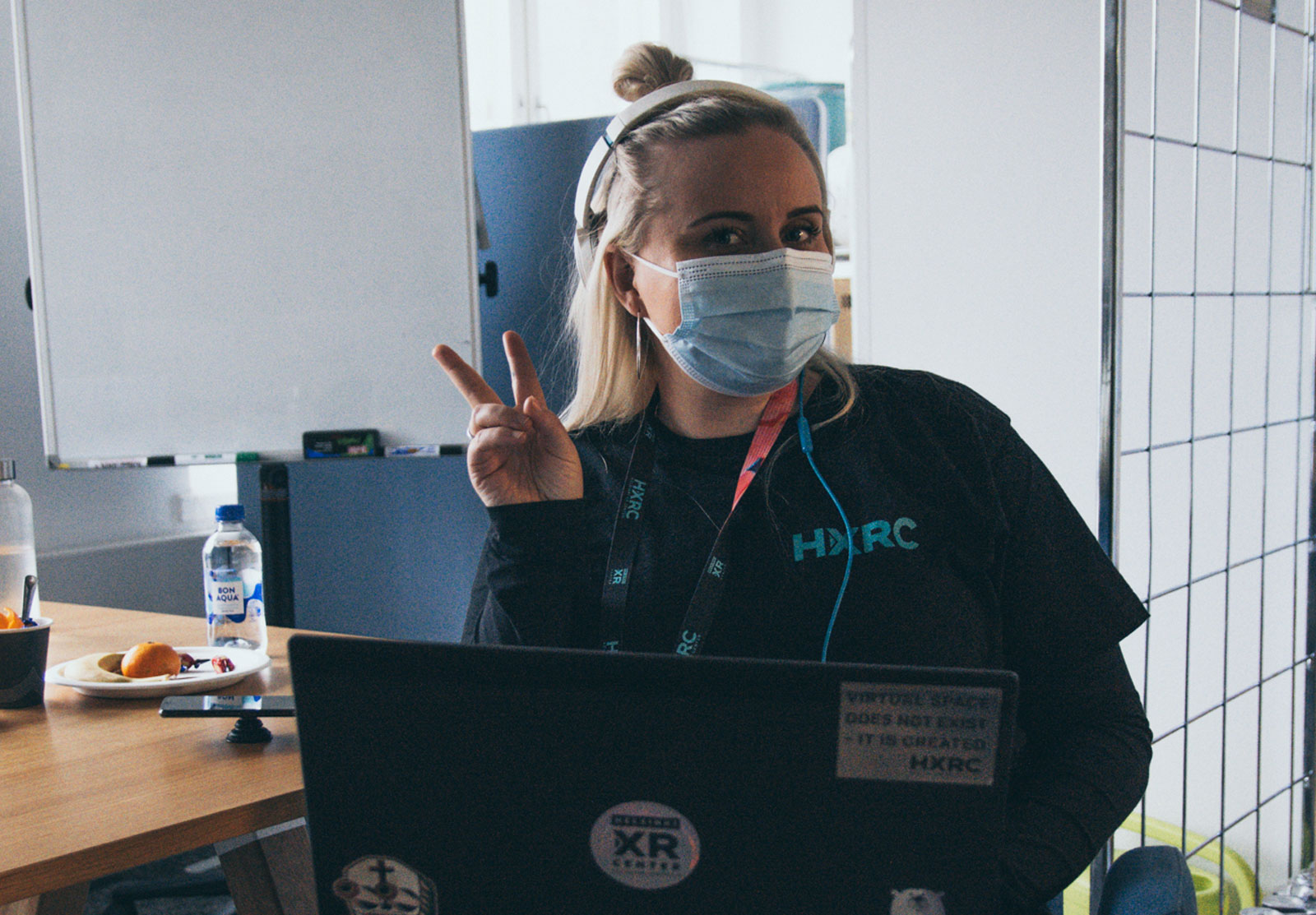 One of the Helsinki XR Center team members sitting, showing a peace sign and smiling with mask on