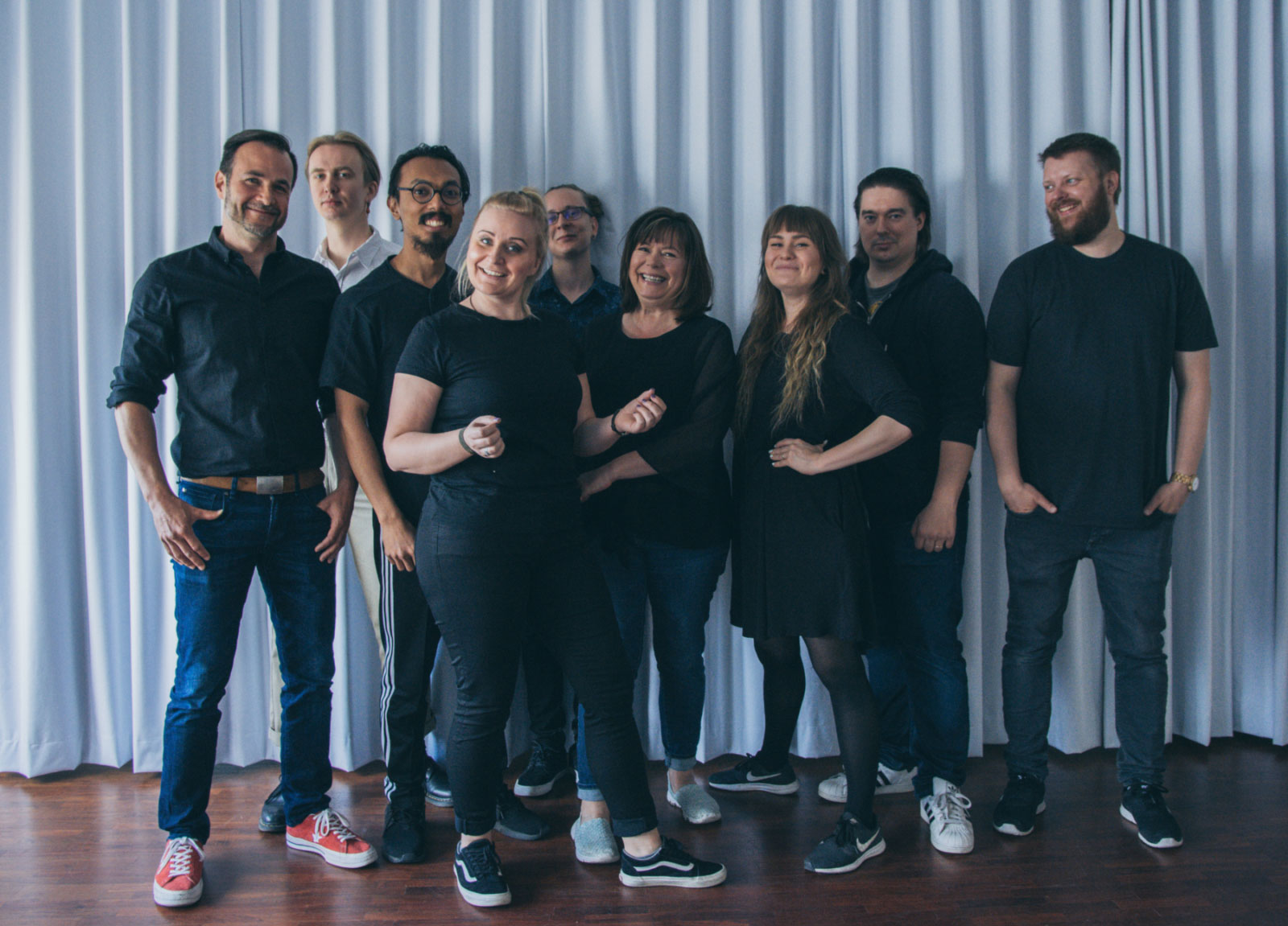 Nine members of the Helsinki XR Center team are standing in front of blue curtain, smiling.
