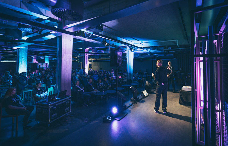 A speaker is standing on a stage in front of a huge crowd at one of Helsinki XR Center's XR activities, the Match XR 2020 event in Helsinki, Finland.