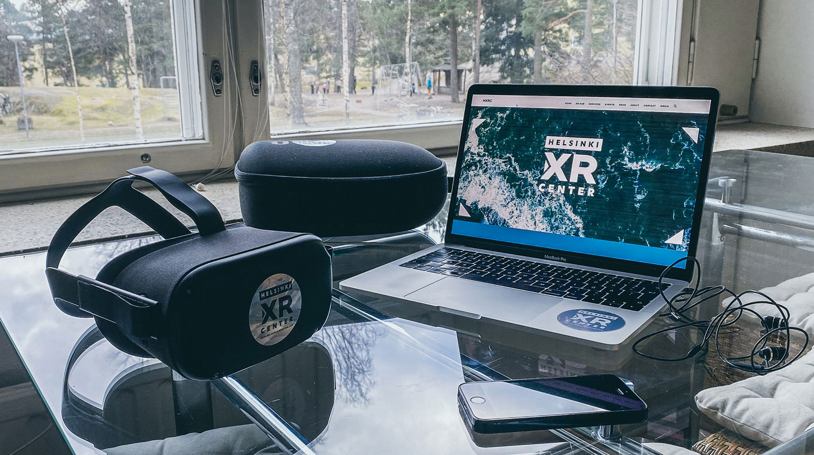 A virtual reality headset, a laptop and a phone on a table in front of a window with a view to a playground surrounded with trees.