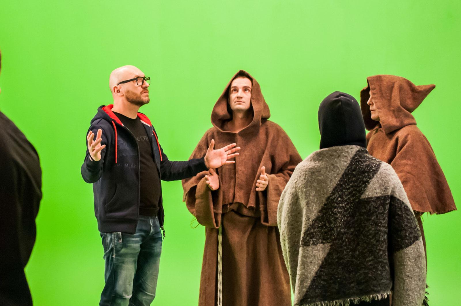 AXiiO's Oleg Nikolaenko directing people dressed as monks in front of a greenscreen.