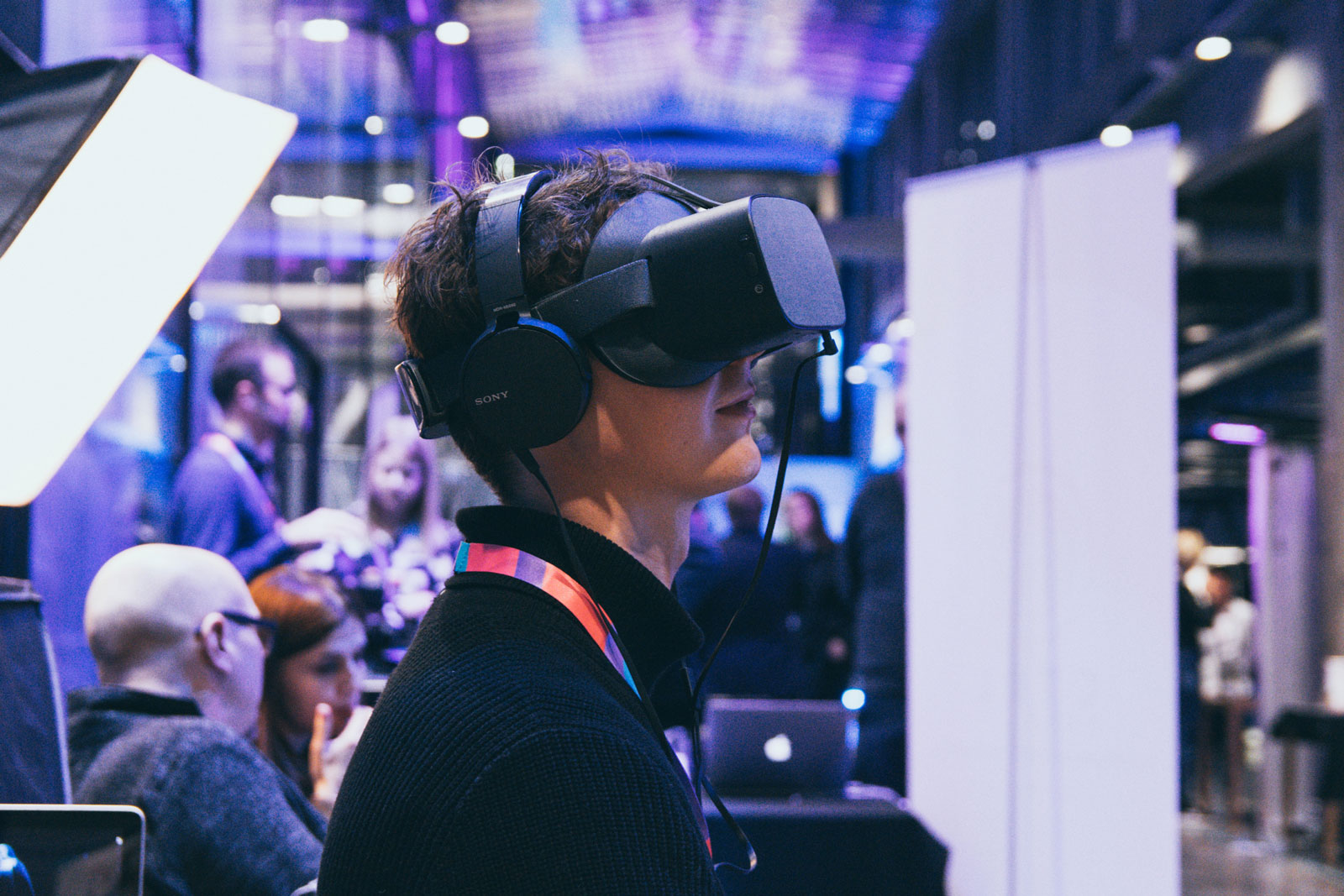 A man with a virtual reality headset on his head is looking up.