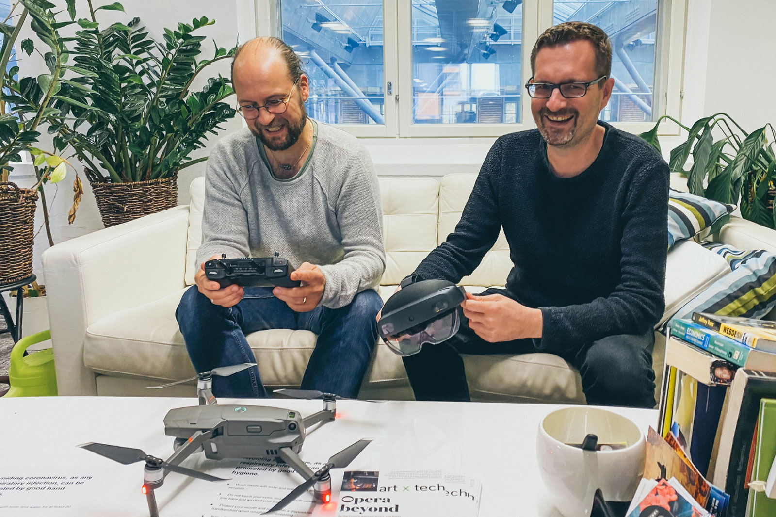 Lassi Immonen and Hannu Lesonen from Anarky Labs. Both are wearing glasses, solid-coloured clothes, and are smiling. In front of them on the table is a small drone.