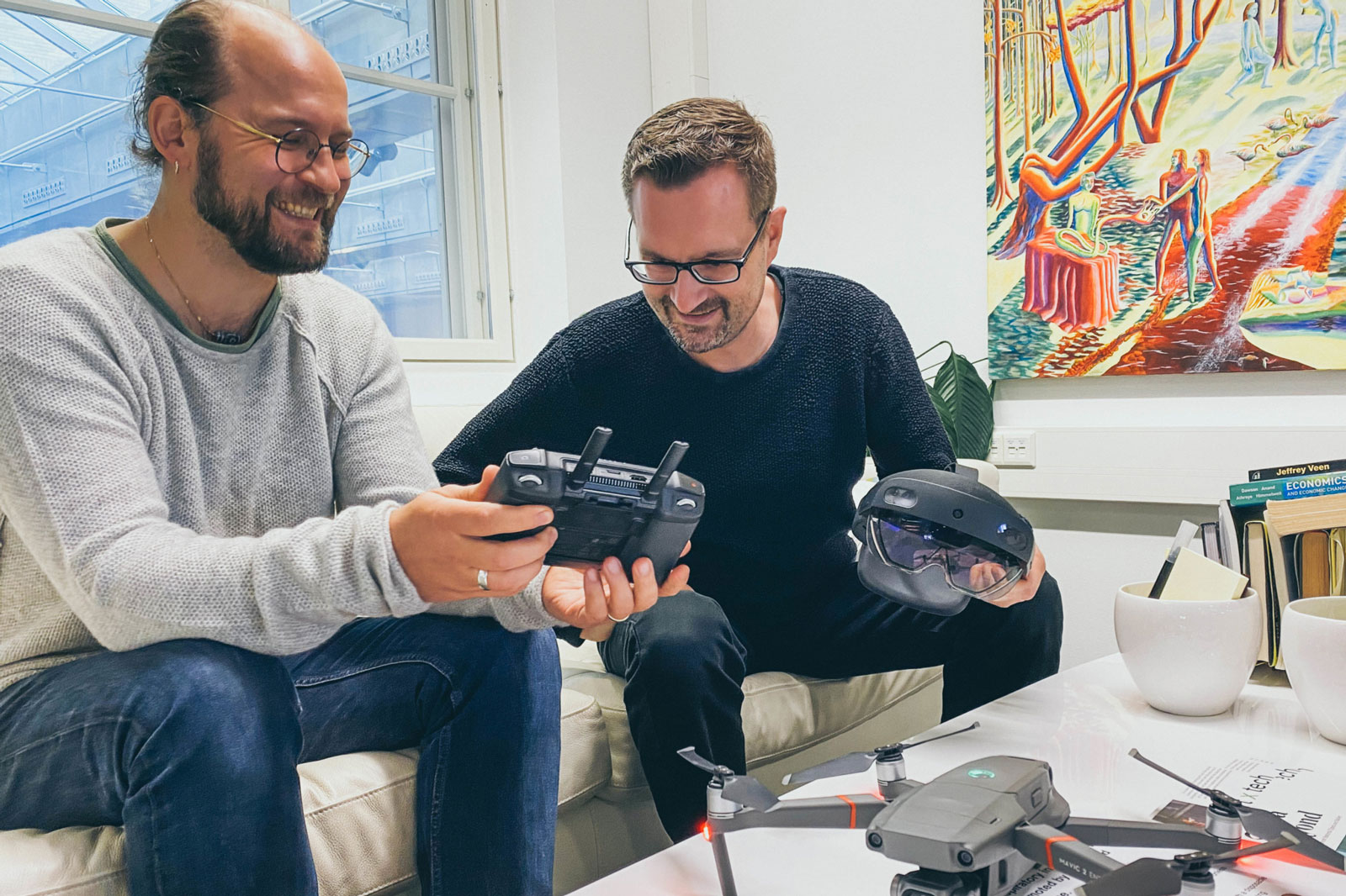 Lassi Immonen and Hannu Lesonen from Anarky Labs examining drone controllers. Both are wearing glasses, solid-coloured clothes, and are smiling.
