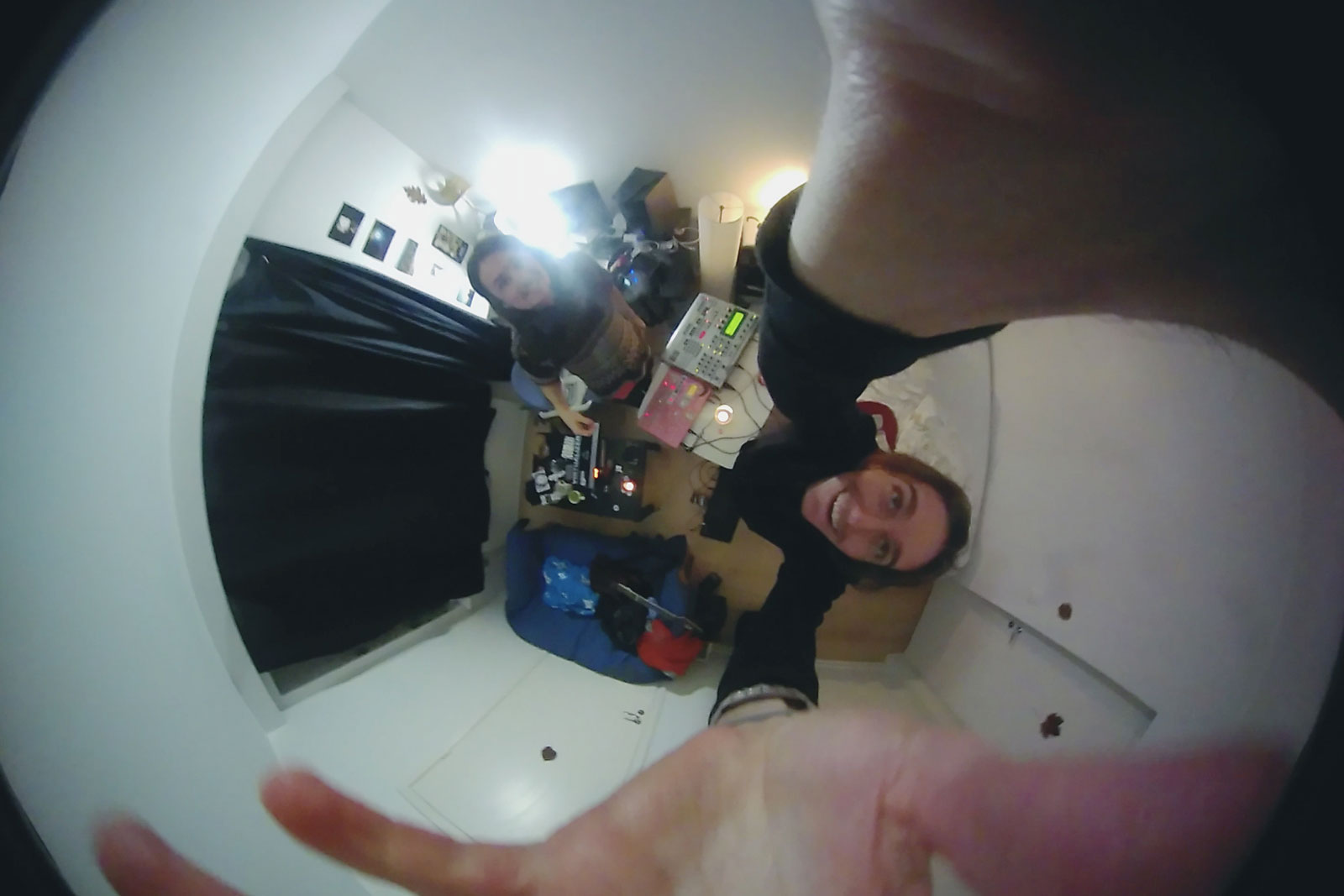 A selfie taken of Unfold Stories' Riccardo and Lucio with a fish-eye lense. They are both smiling, and it seems like the whole room is spinning around them.