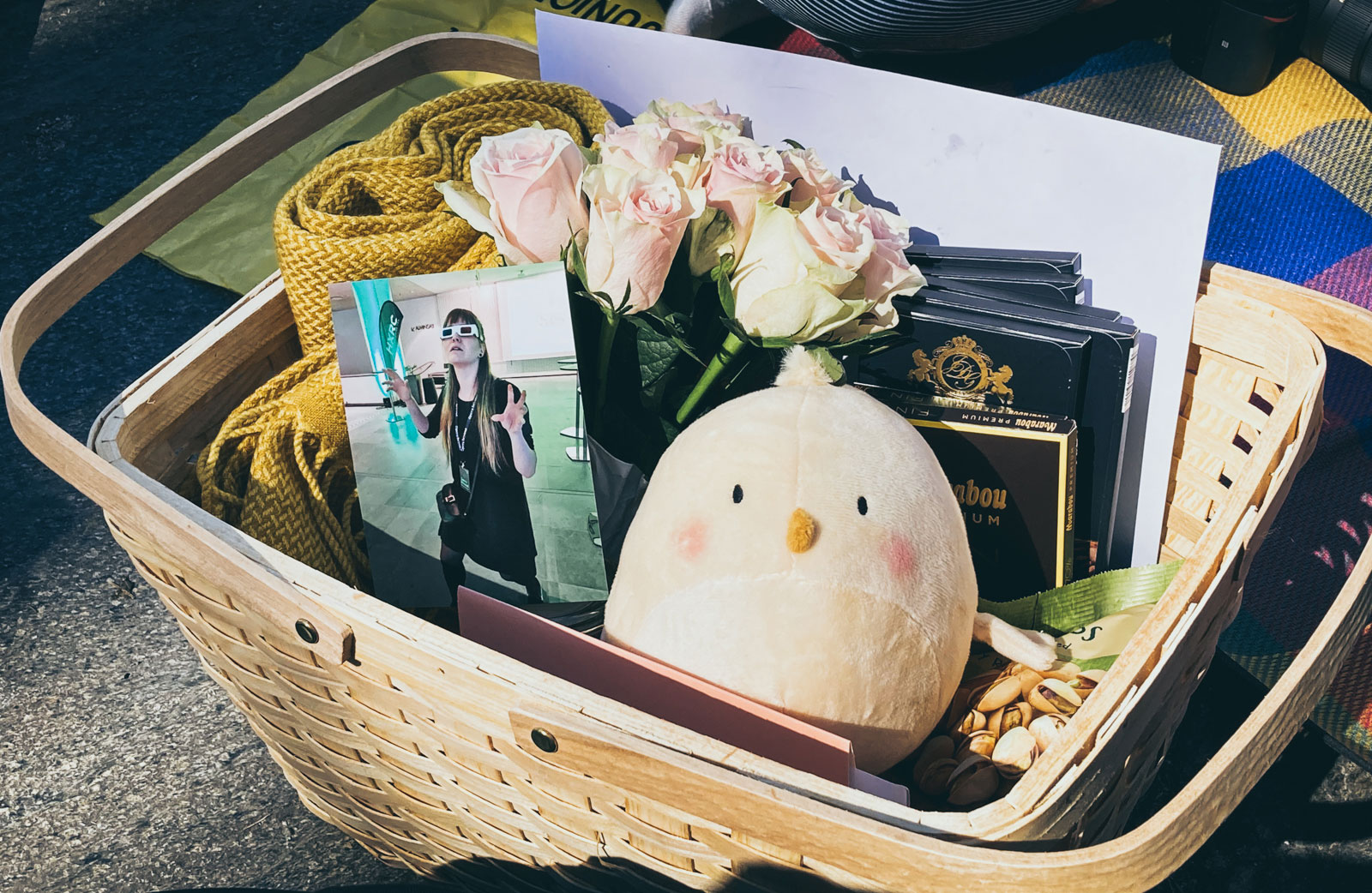 A gift basket with a photo, a chick plushie, chocolate, and roses.