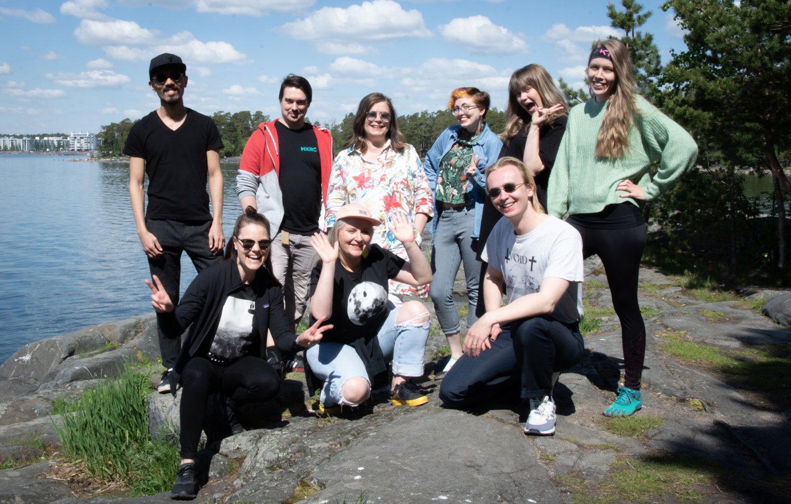 Nine members of the Helsinki XR Center team posing on a cliff by the sea.
