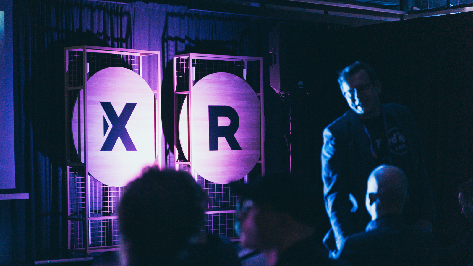 Purple-tinted event space with the letters X R visible in the background.