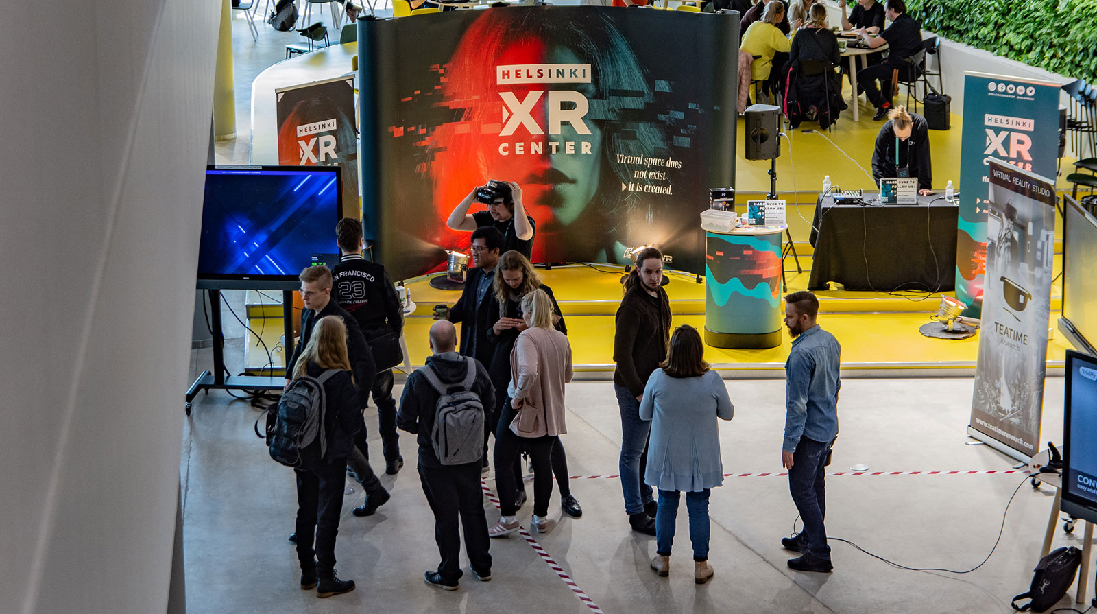 A roadshow VR stand in a large convention area, with people trying out headsets.
